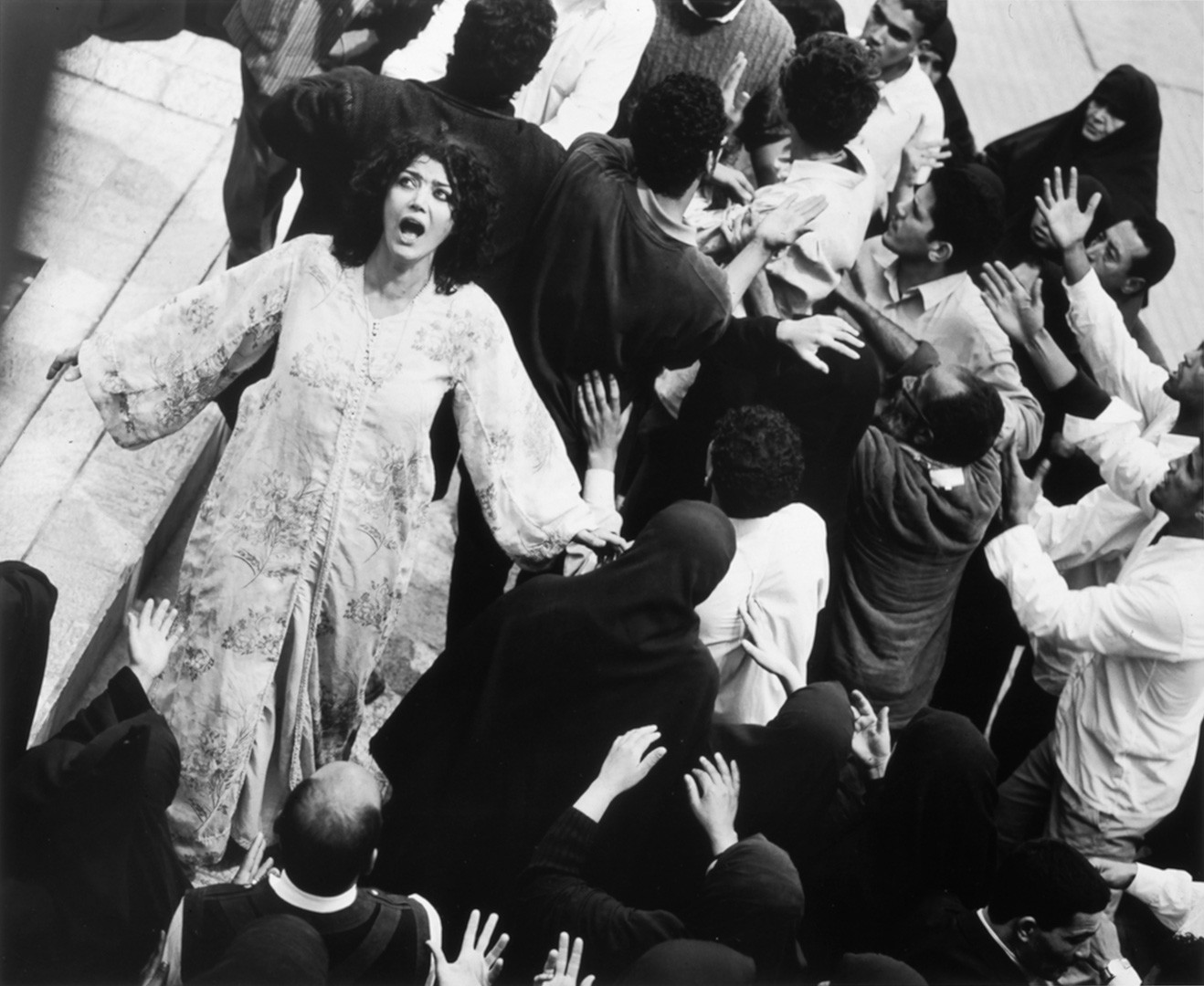 In the midst of an arguing crowd in traditional Iranian dress, a woman without a veil wails, arms out to her sides.