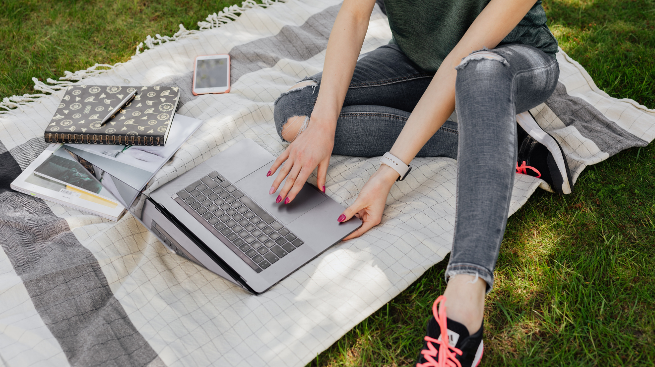 Woman sitting on blanket in grass while working on a laptop