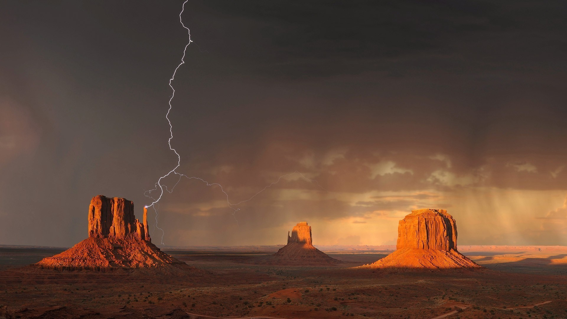 Three formations in Monument Valley Arizona. This one has a bolt of lightning touching the point of a formation
