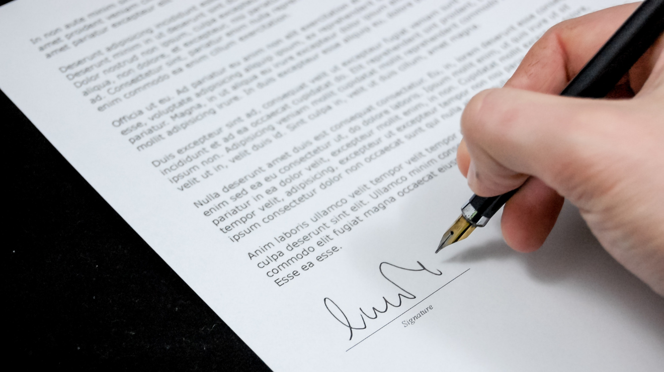 White hand with fountain pen signs a fake legal document on white paper