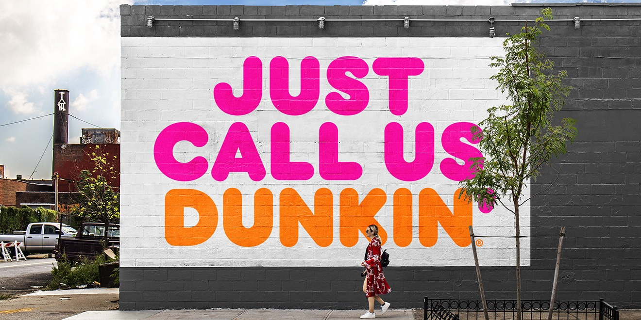 Dunkin Donuts wall messaging with woman standing in front
