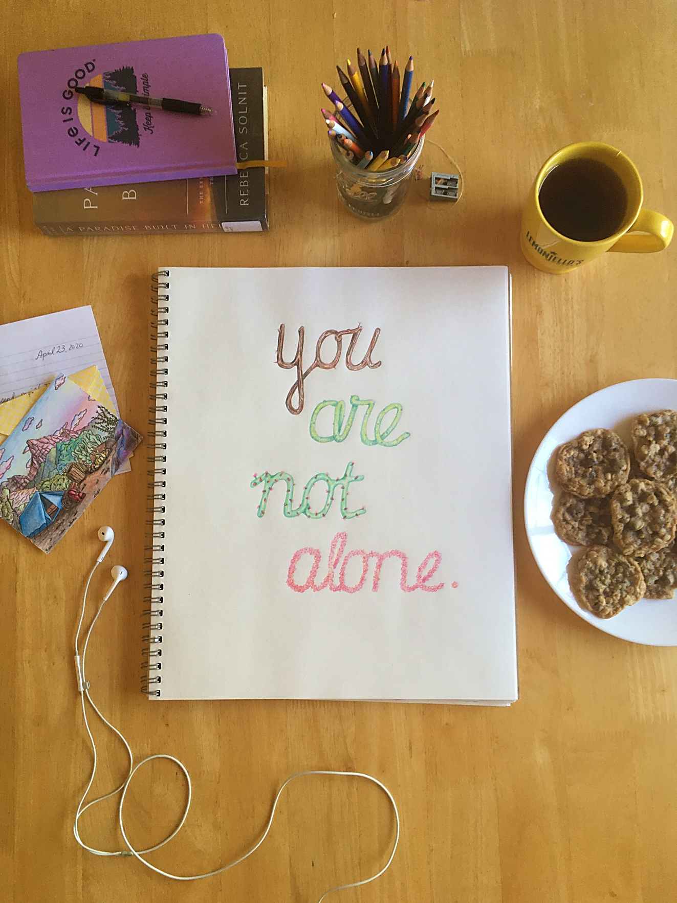 """A drawing pad with the words """"you are not alone."""" Framing the page are headphones, a journal, a mug of tea, and cookies."""