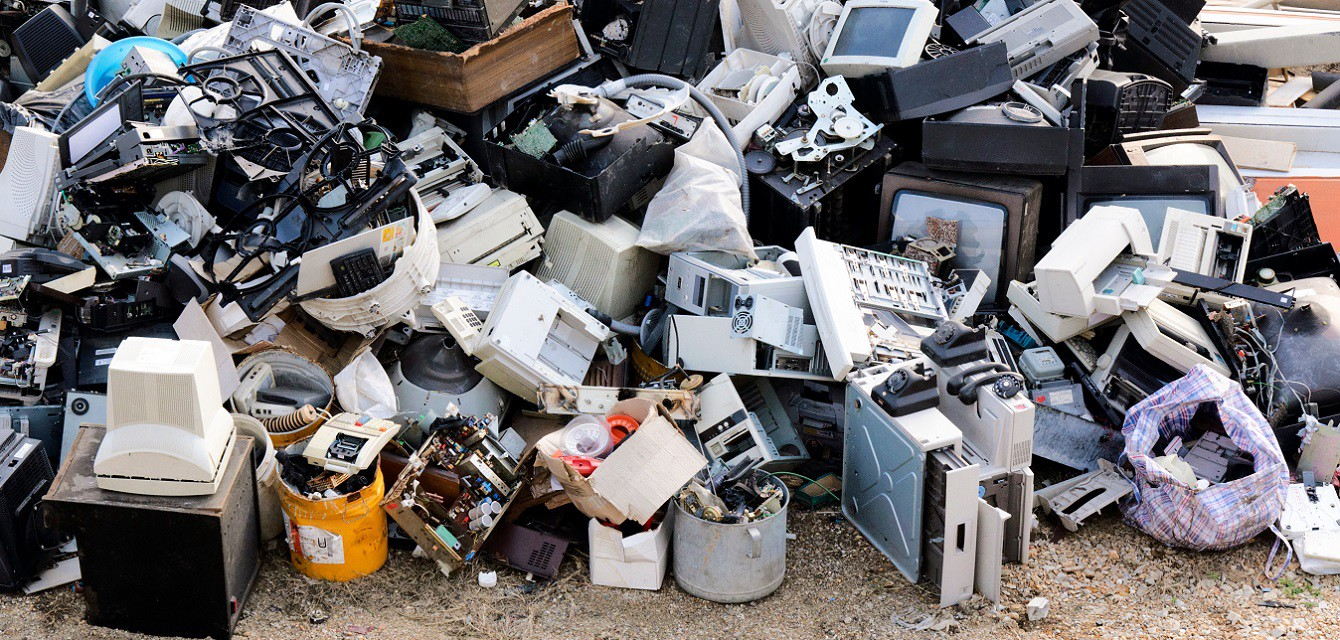 A large pile of discarded electronic gadgets on a waste dump including computers and tvs