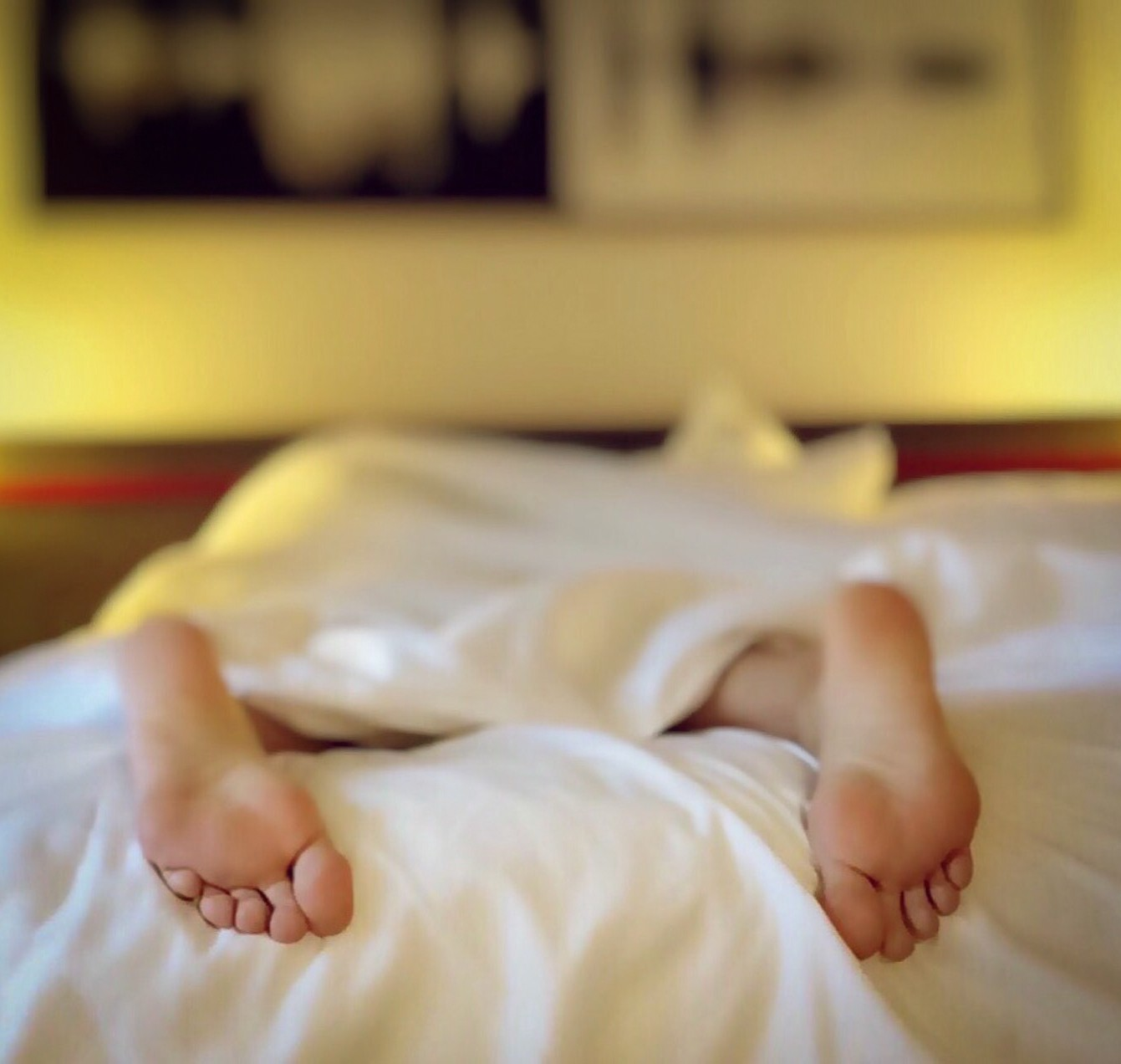 Comatose person in bed. All we see are their soles, pointed down. They are out of it!