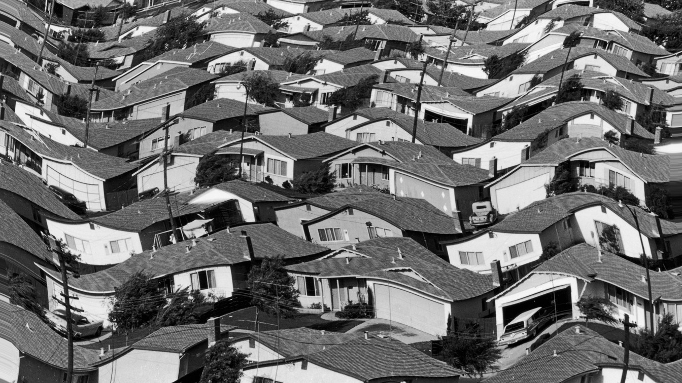 Vintage black-and-white photo of a densely populated suburban neighborhood of single-family homes. A wavy effect has been added to the photo.