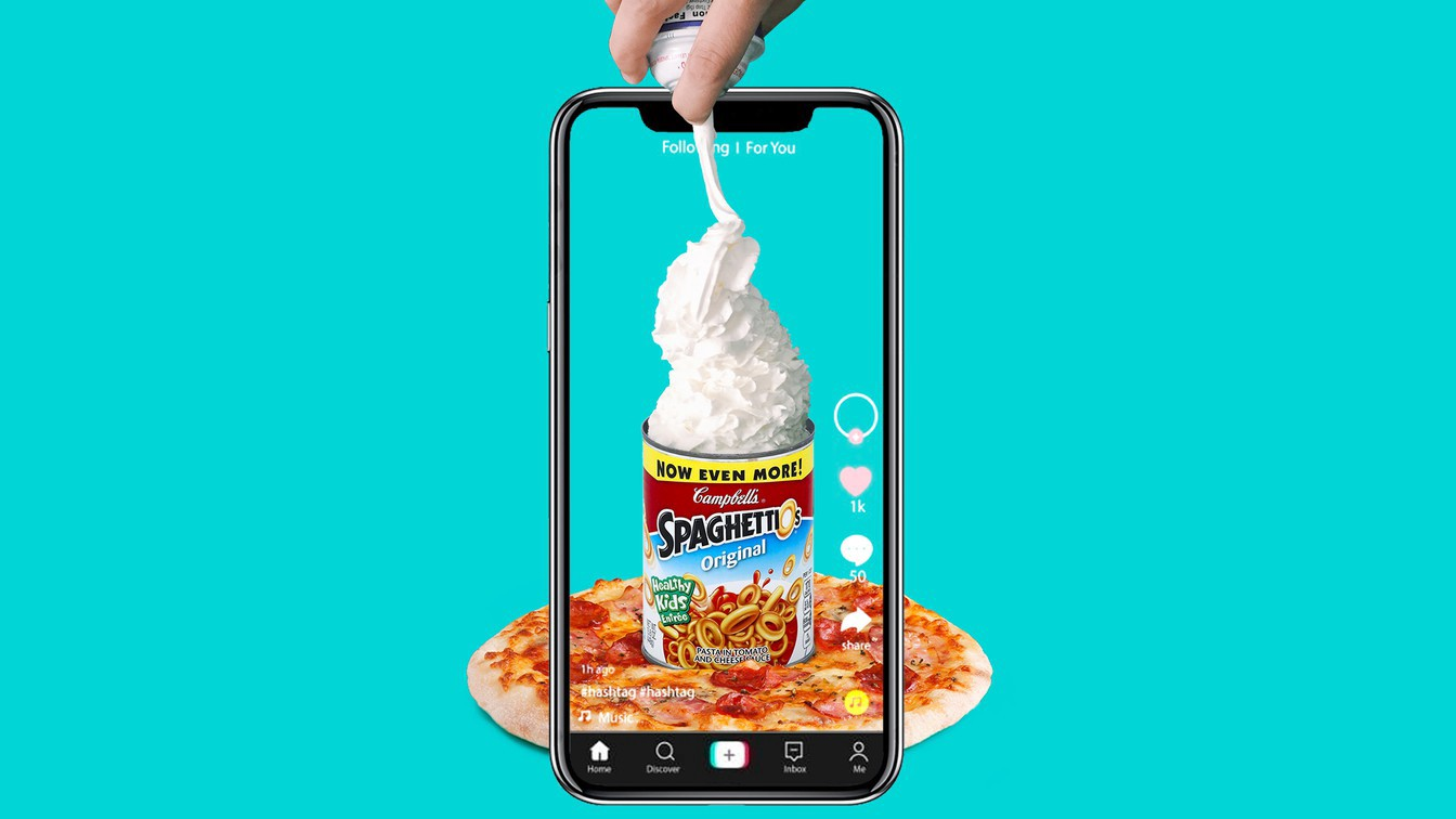 A cellphone with a TikTok-like app with a can of Spaghetti-os, a hand spraying whipped cream into it, on a pizza.
