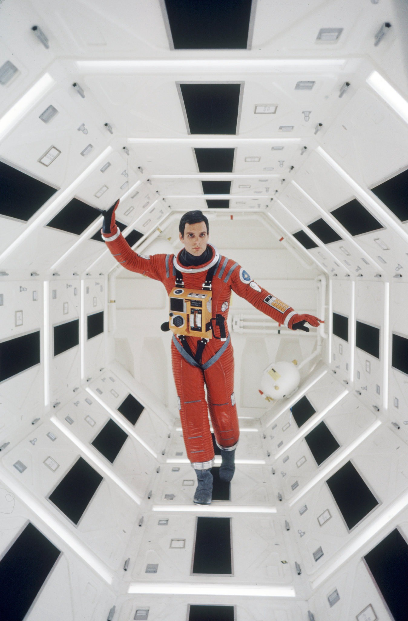 A picture from the movie 2001: A Space Odyssey. A astronaut floats in a futuristic white corridor while on a spaceship.