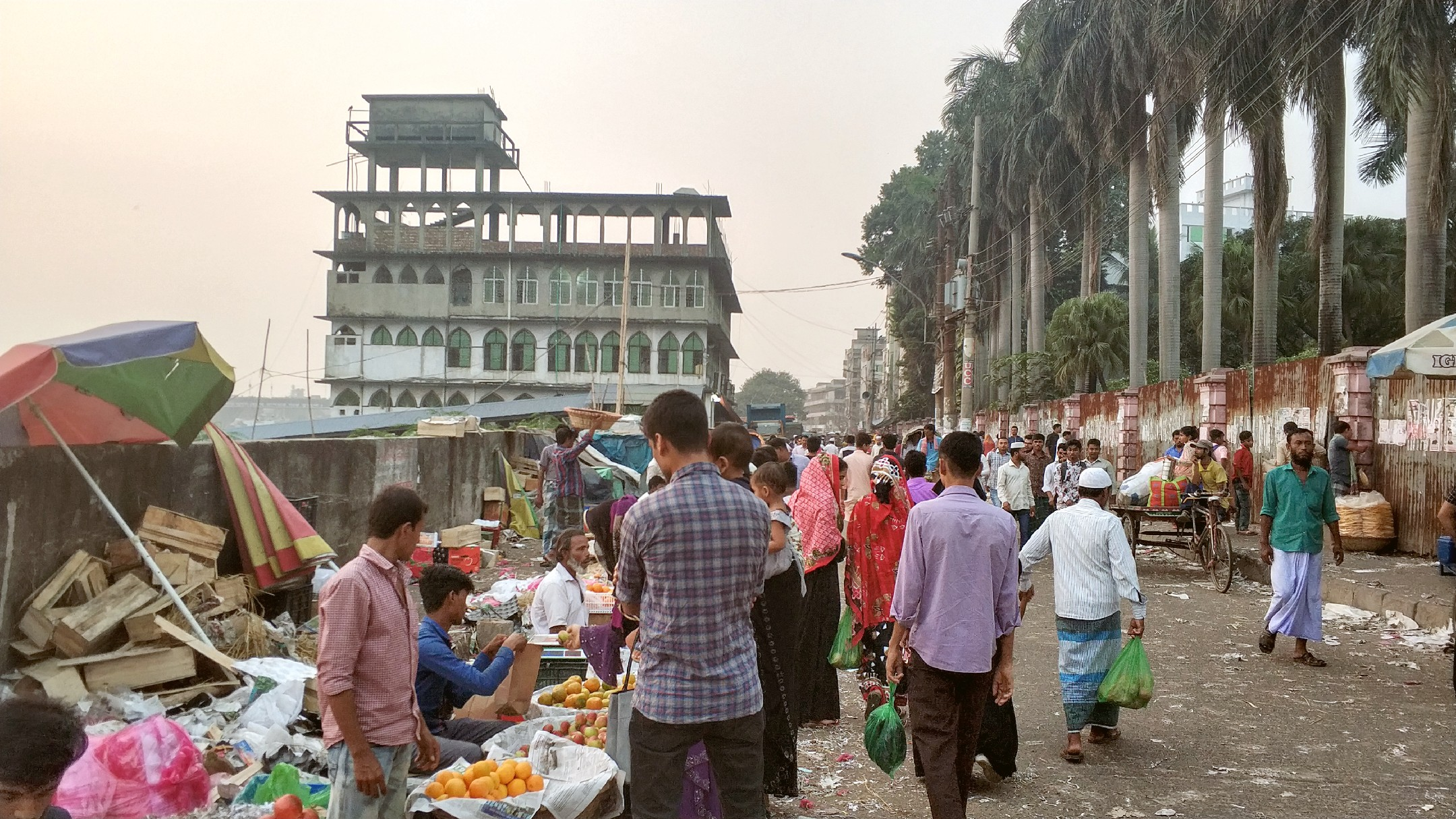 Fruit sellers tending to customers along the trash filled roads near the Buriganga River