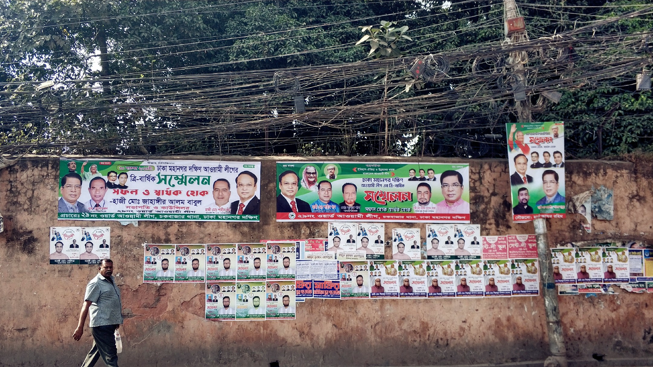 Man walks past political posters in Dhaka