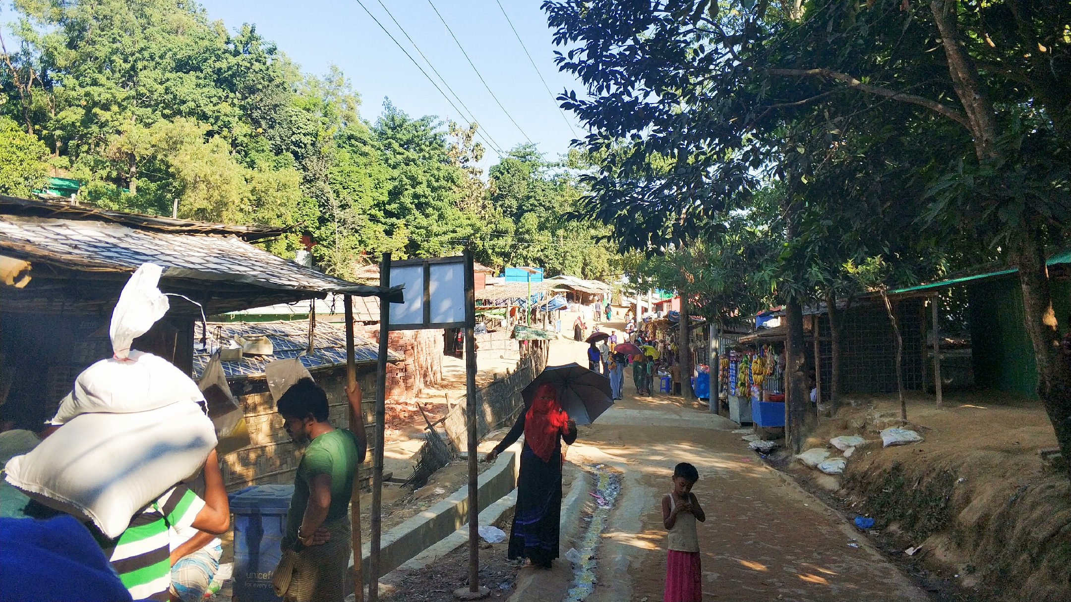 Paved roads inside the camp filled with busy pedestrians and playful children at kutupalong refugee camp