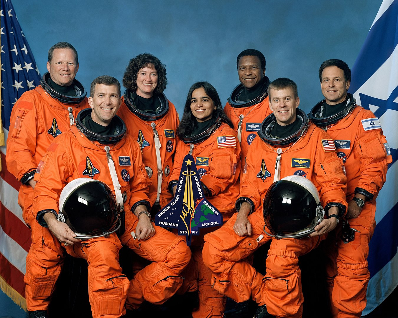 A crew of seven astronauts pose in spacesuits.