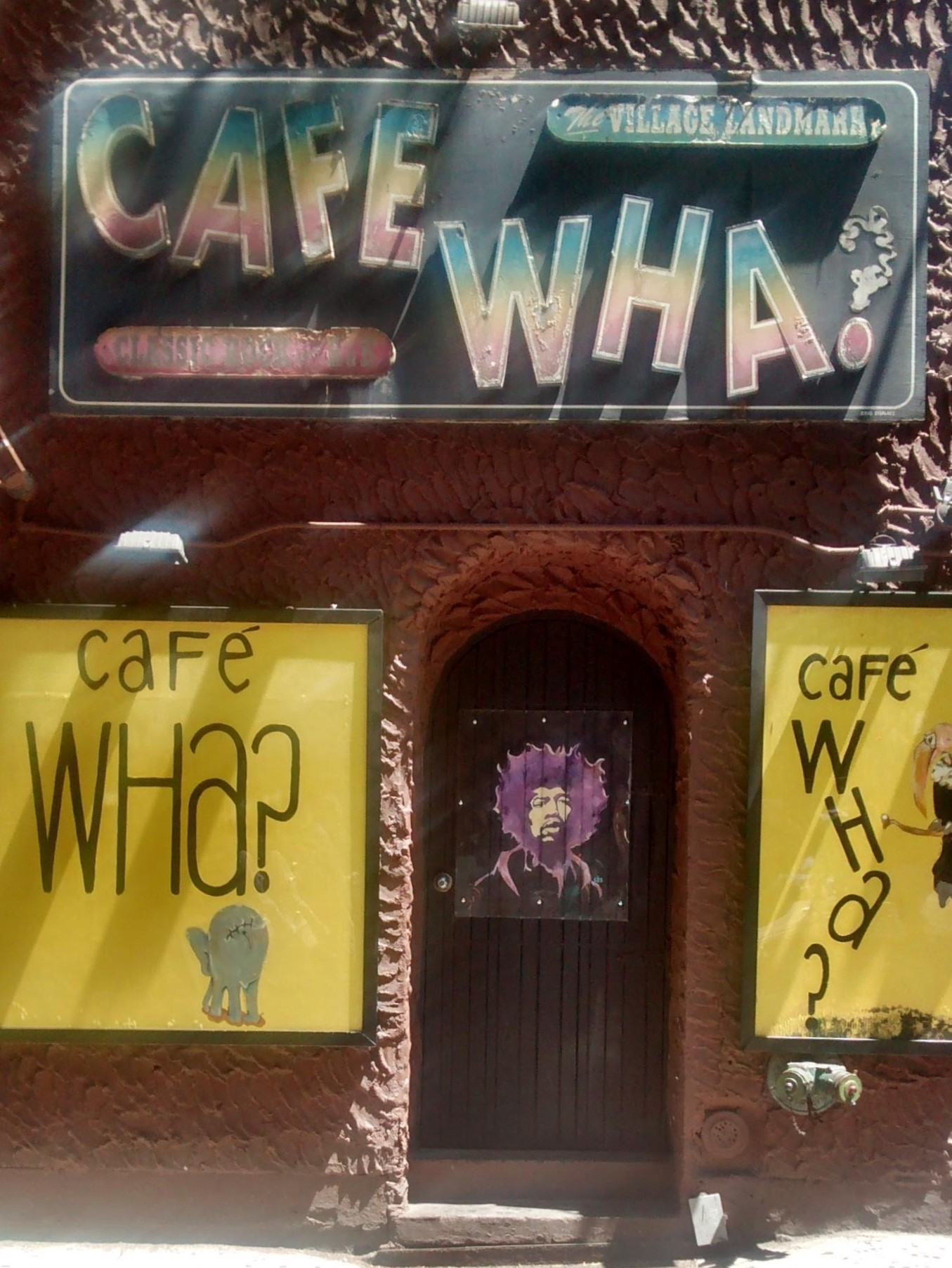 """Exterior of """"Café Wha?"""" with poster of Jimi Hendrix on the door."""