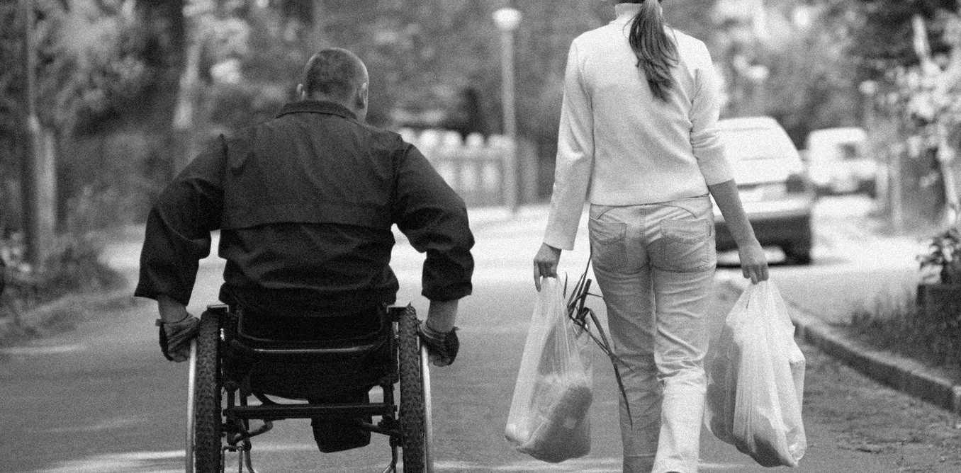A man in a wheelchair next to a lady walking and carrying grocery bags with food.