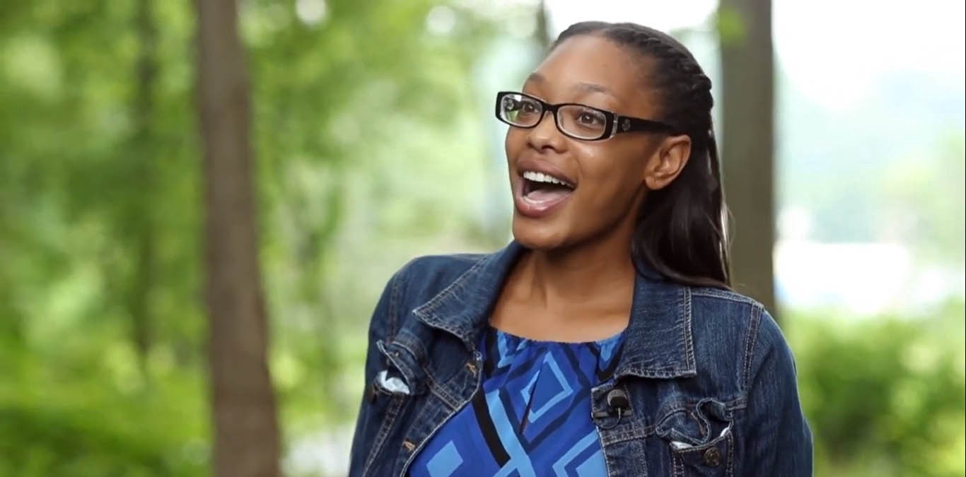 A young black woman wearing glasses, hair half up, jean jacket, blue shirt standing outside among trees. She's speaking.