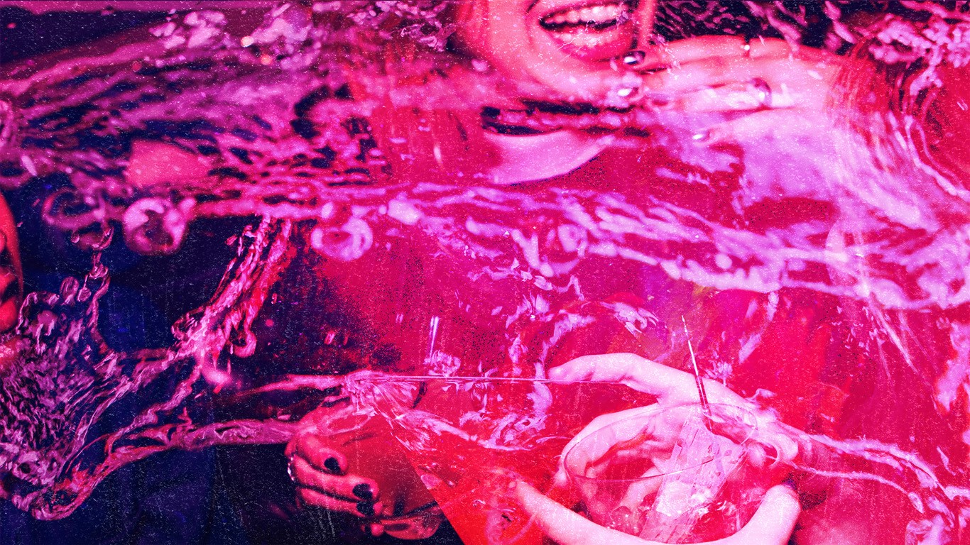 A double exposure in magenta, bottom image is of someone laughing and talking, holding cocktails, top image is liquid spilling across the frame.