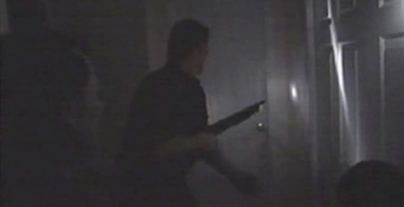 In a dark corridor, a man brandishing a shotgun is ready to open a door.