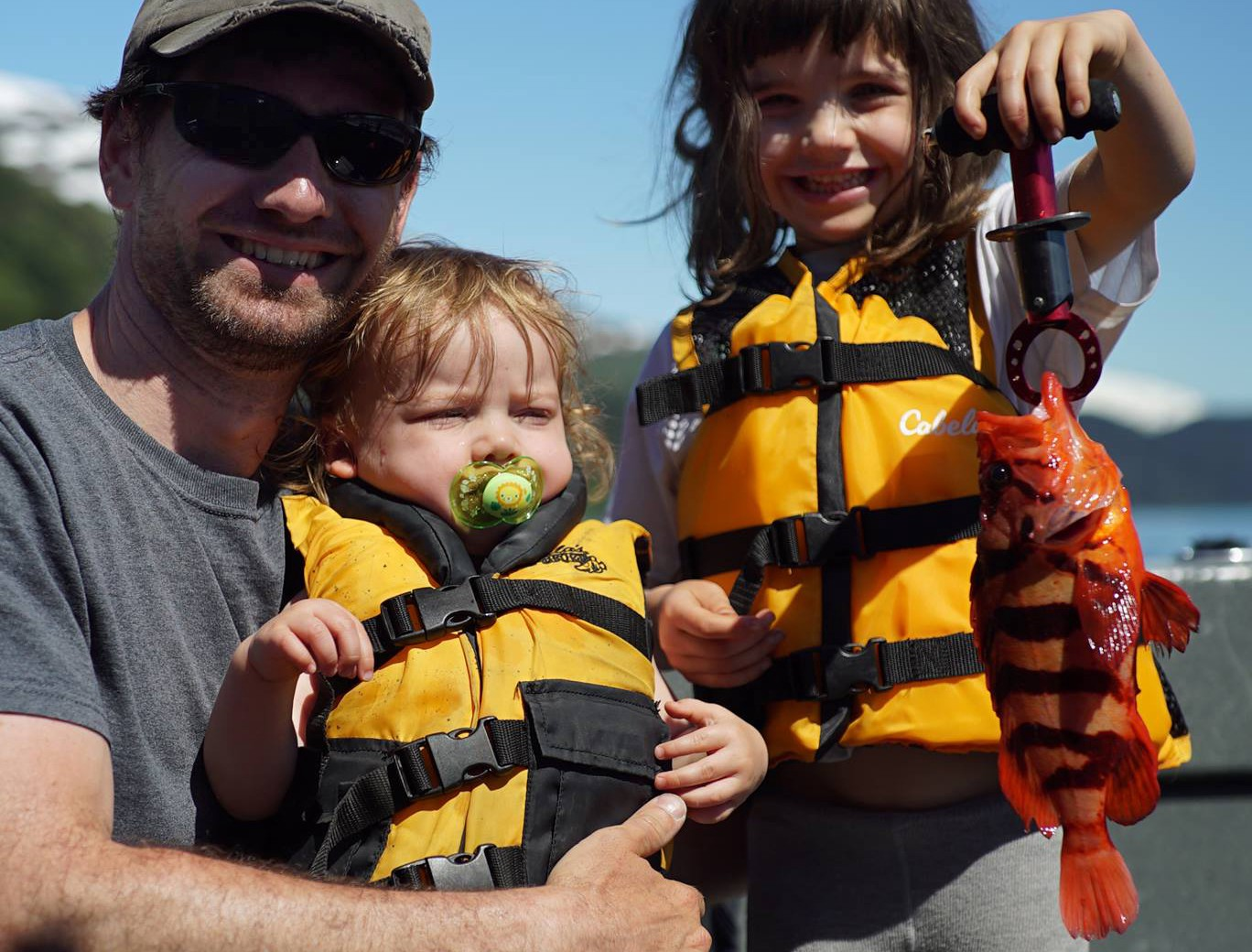 young girl holding a striped orange rockfish with her baby brother and dad