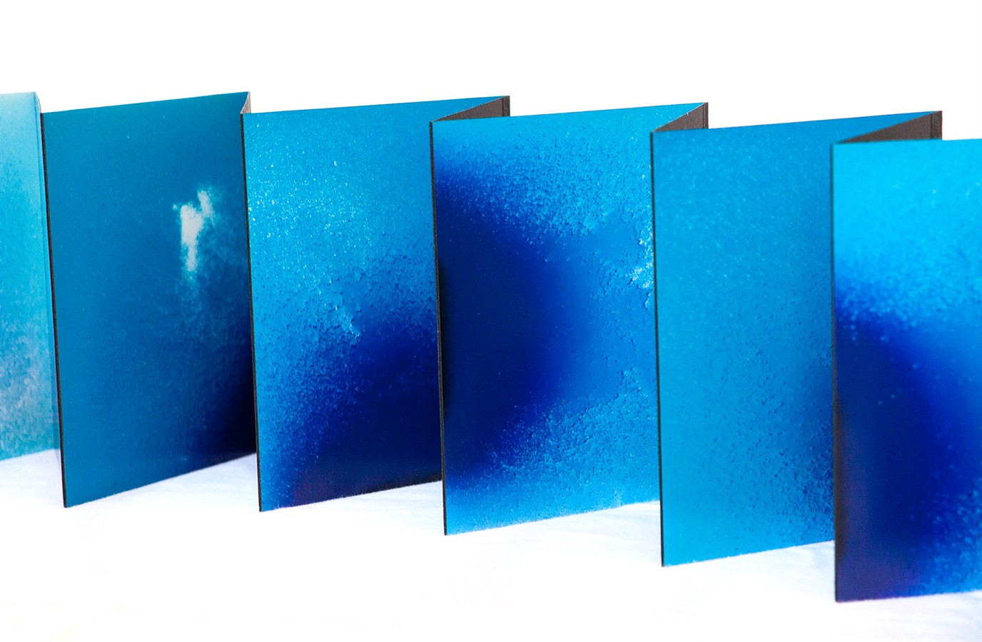 Saturated blue pages of an art book accordion out, zigzagging across the photo.
