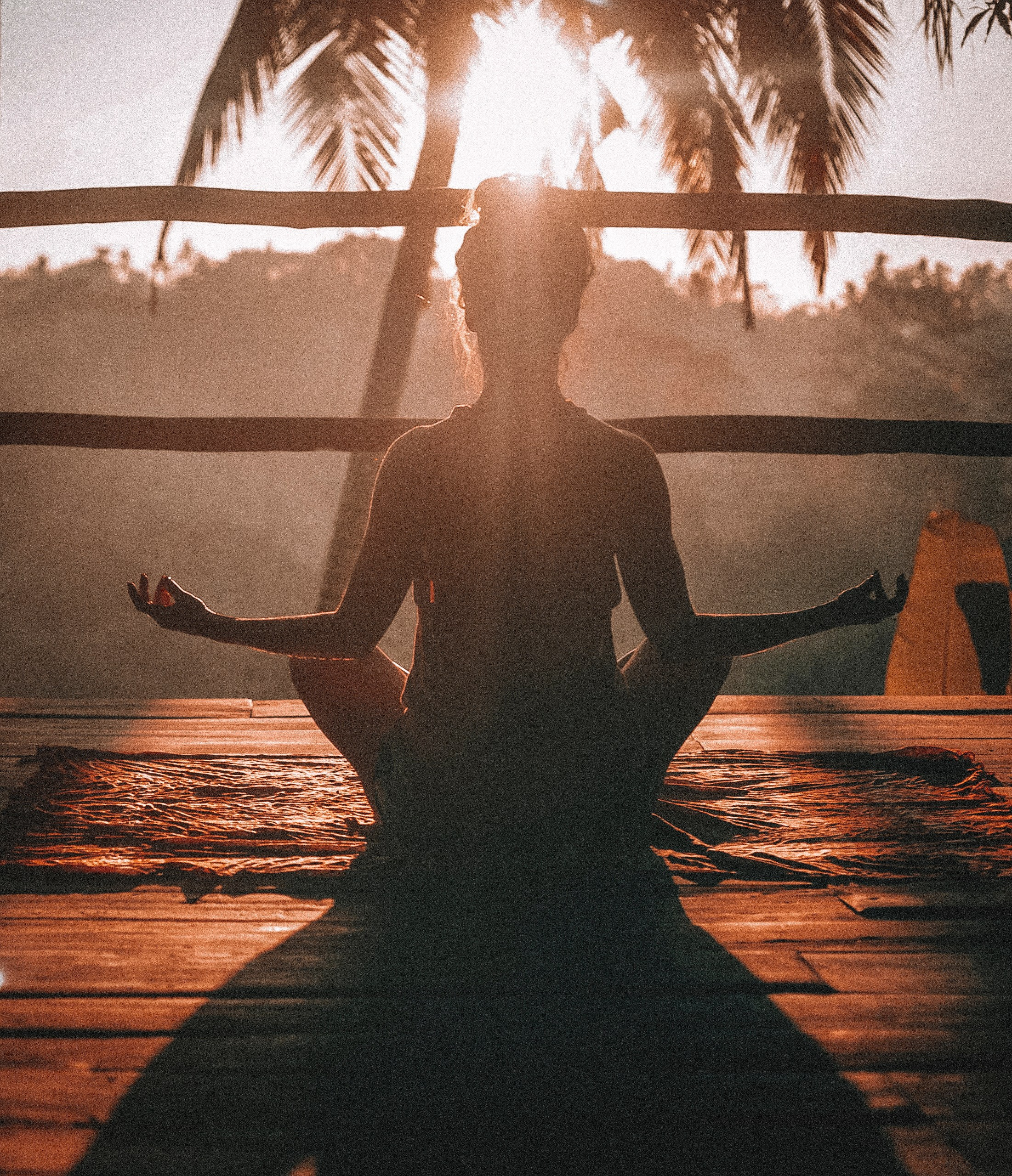 Woman meditates (or does yoga) before a sunrise/sunset in a tropical location.