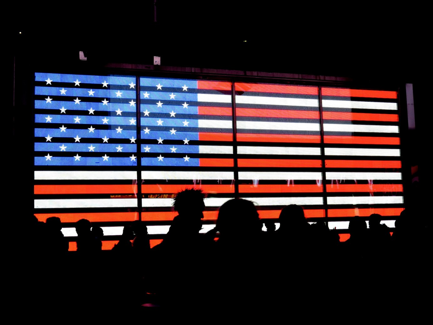 A group of people in silhouette in front of a projection of the American flag.