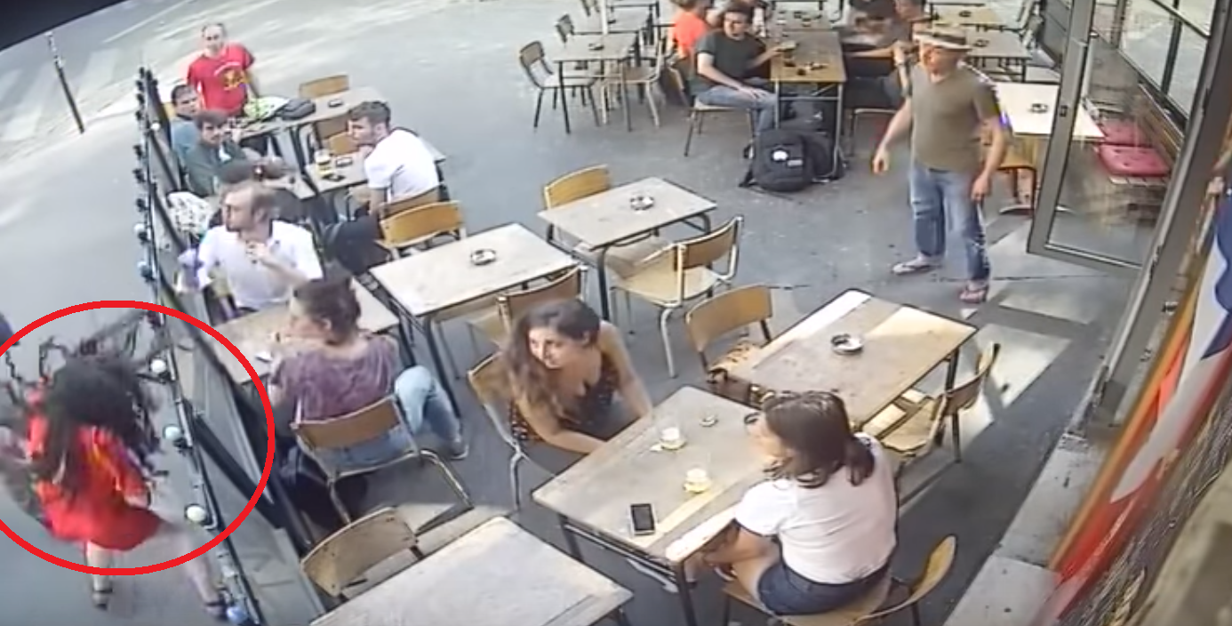 A security camera image of an entitled man with a fragile ego punching a woman outside a café in France