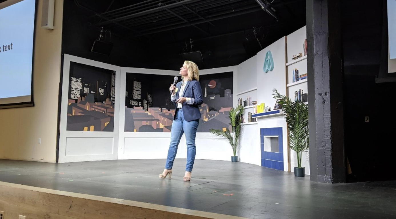 Ashlee Phillips (that's me) striking a confident pose on stage at AirBnB as she delivers her talk on web accessibility.