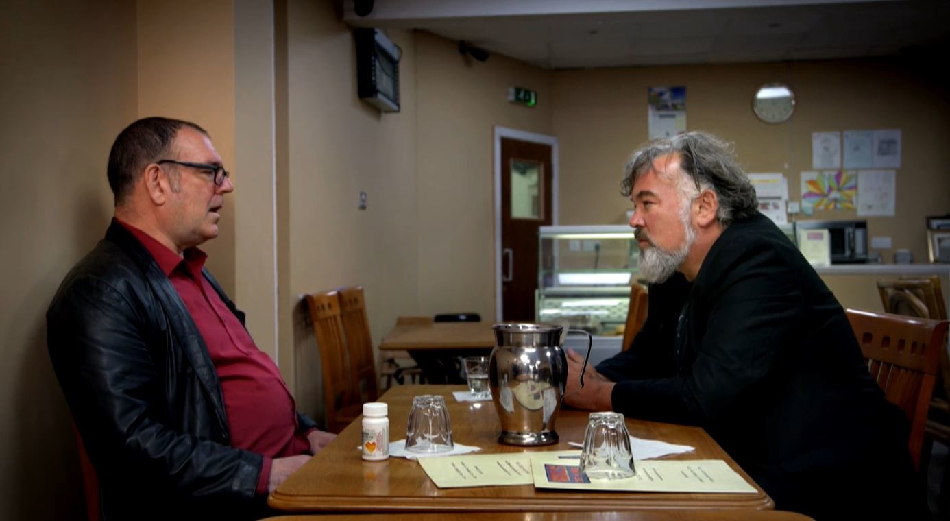 Robert Lloyd and Stewart Lee chat in a cafe in a scene from the documentary, King Rocker.
