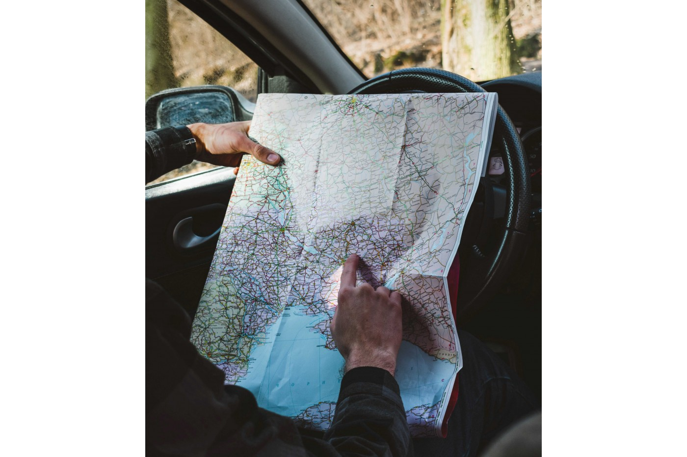 A man holding a map over his car's steering wheel and figuring out his location and course.