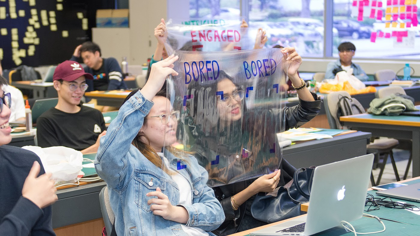 A classroom of students demonstrating an AI prototype. They are holding clear acetate sheets in front of their faces. Each sheet has a drawing of a frame with words above it—bored, engaged, intrigued.