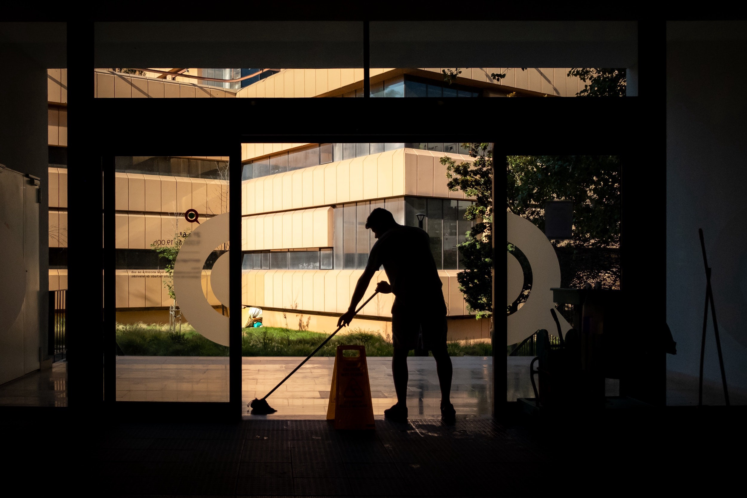 Person mops entryway of newly opened building