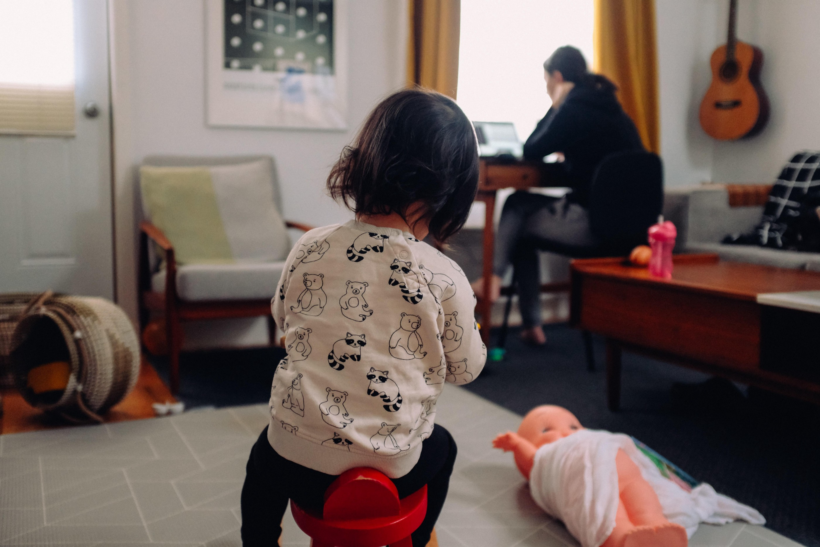 Mother working from home with small child in foreground