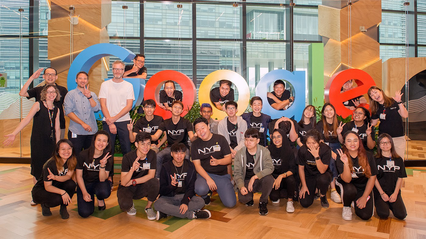 Group photo of students and workshop moderators posing in front of a large Google logo.