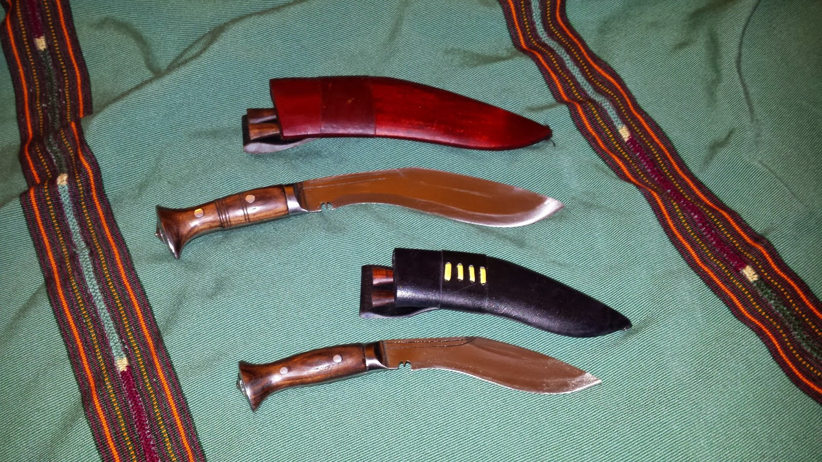 """Kukri knives with 10"""" and 7"""" blades laid out on an unmade bed"""