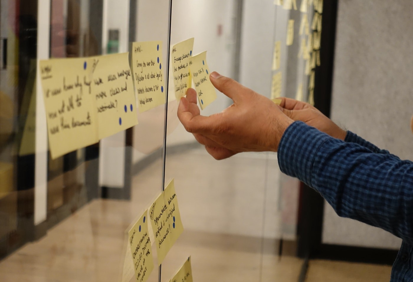 Rearranging Post-it notes on a glass wall during a Design Sprint