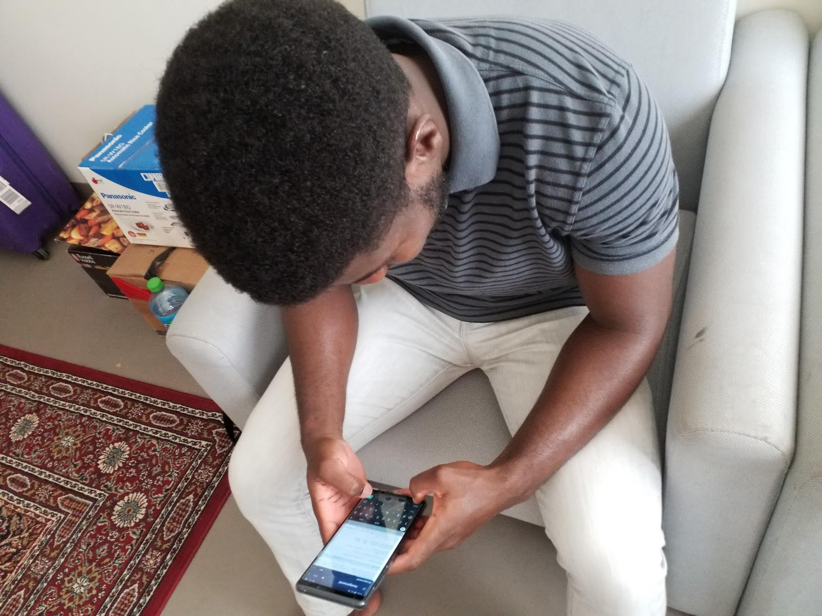 A young African man holds his smartphone. The screen shows a coding window. He leans over it and types with his thumbs.