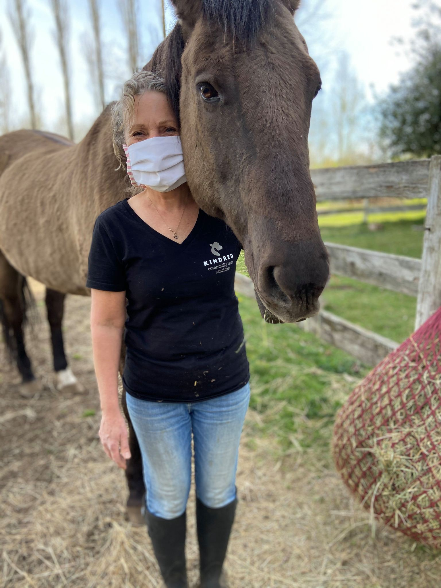 Keryn Denroche, a woman with short gray hair and a gray mask, poses with a soft looking brown horse on her farm sanctuary