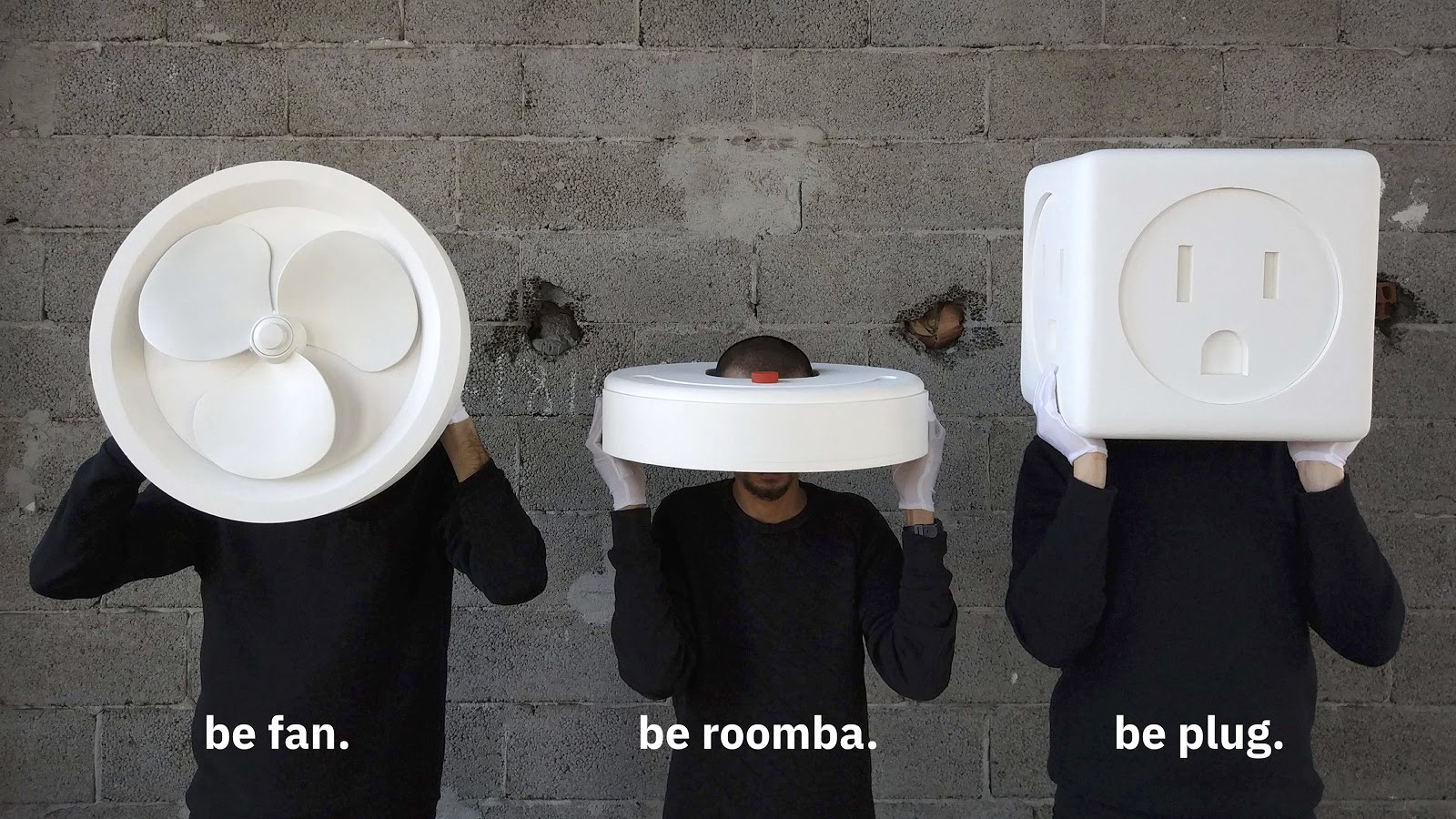 Three people with large household objects on their heads covering their eyes: a fan, a roomba, and a plug.