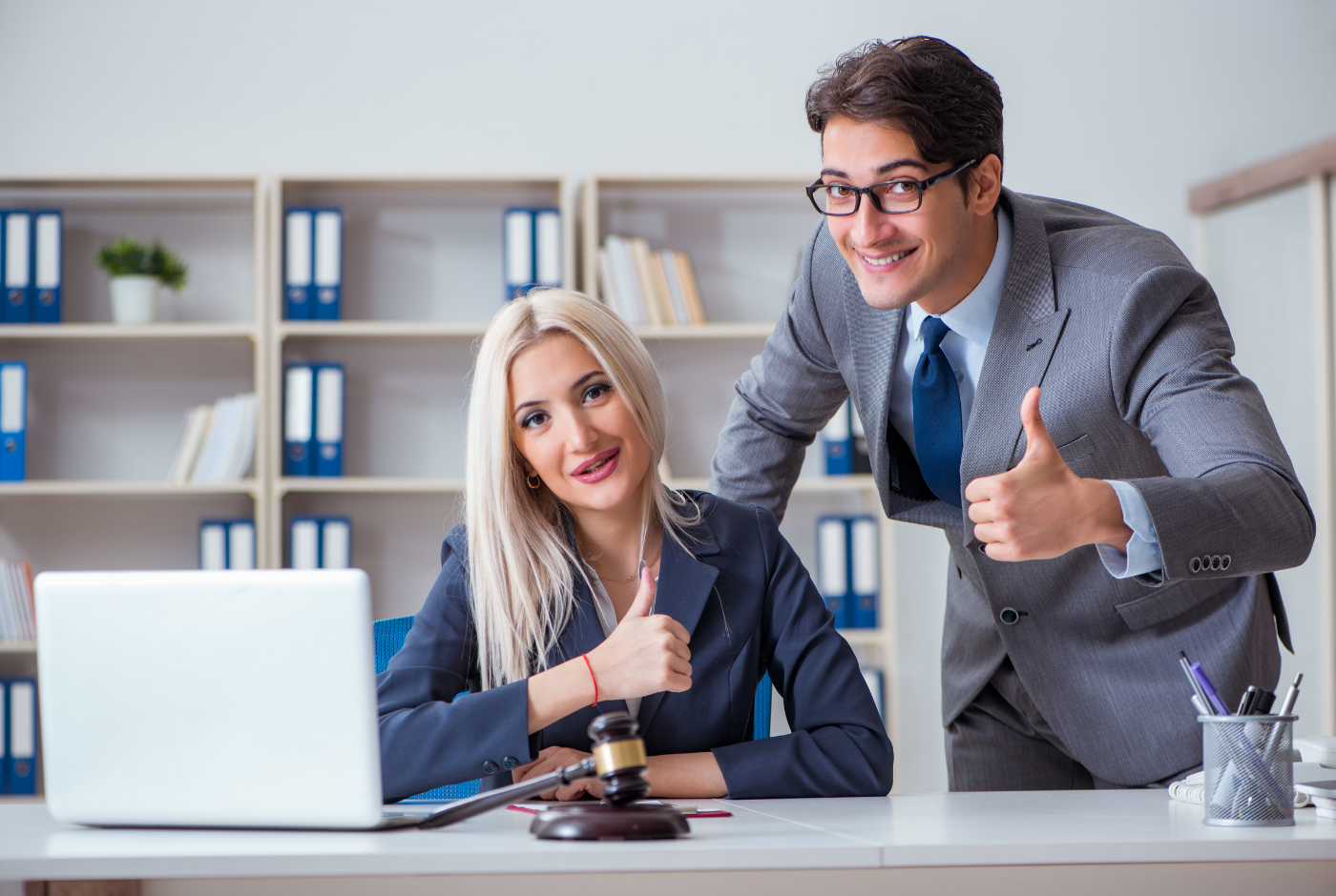Professional man and woman in business suits with fake smiles at desk with laptop and gavel on it.