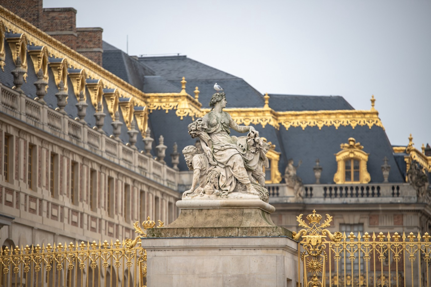 Gilded accents and a statue of a woman outside the Château de Versailles.