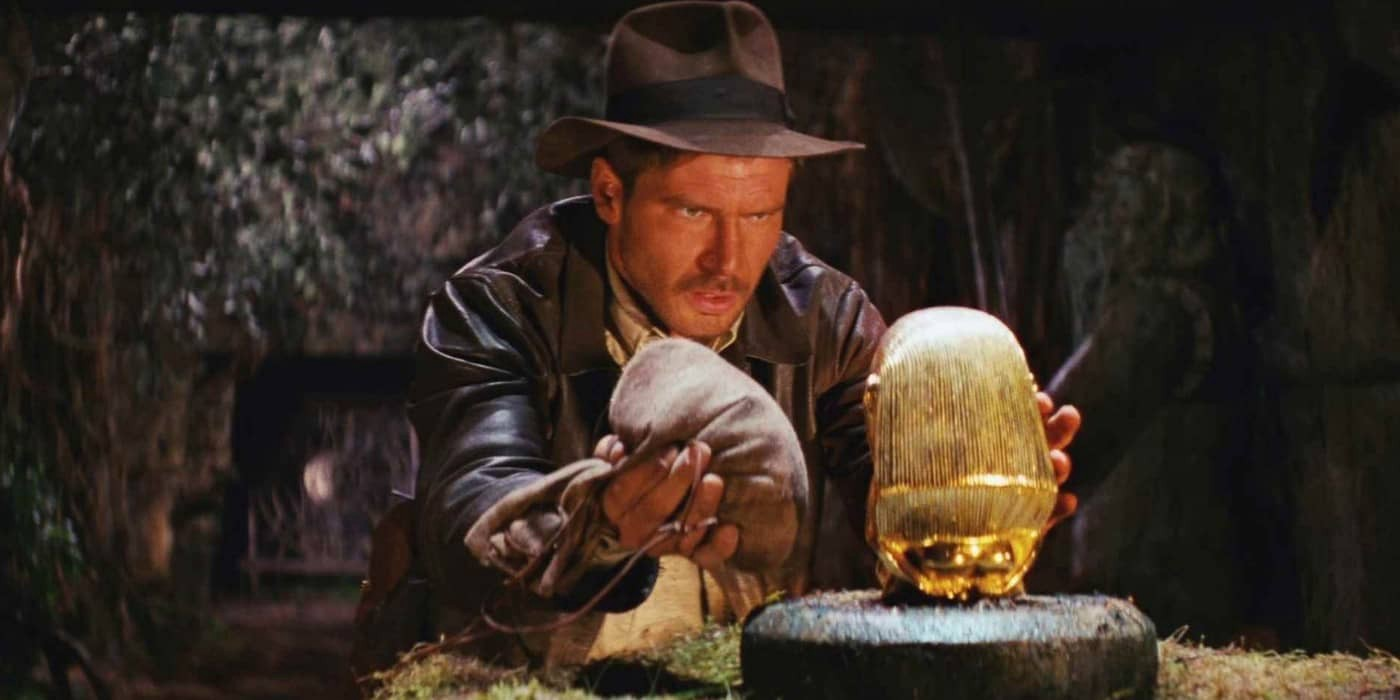 Indiana Jones preparing to grab an idol from a pedestal
