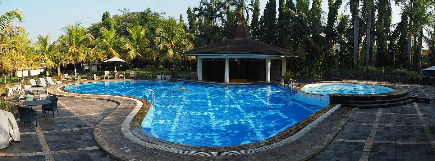A panoramic view of a hotel pool, with sun loungers in the background