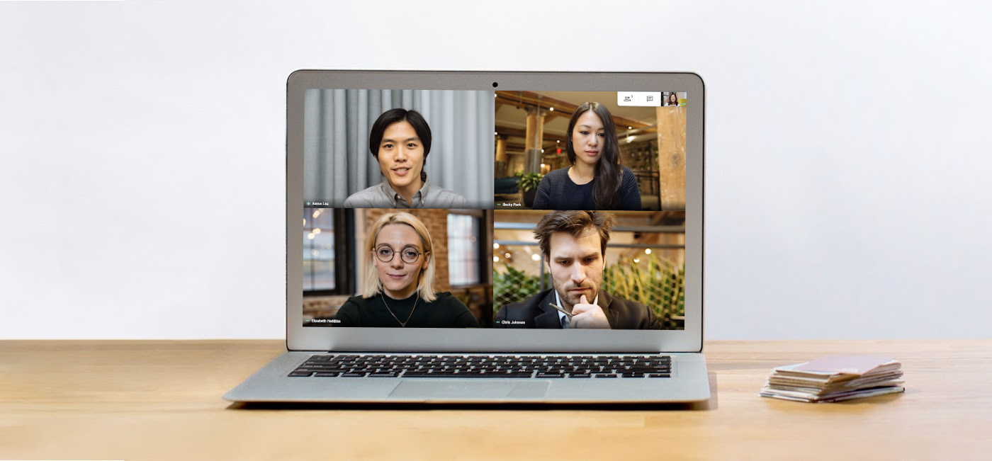 A laptop on a desk features a videoconference of 4 people