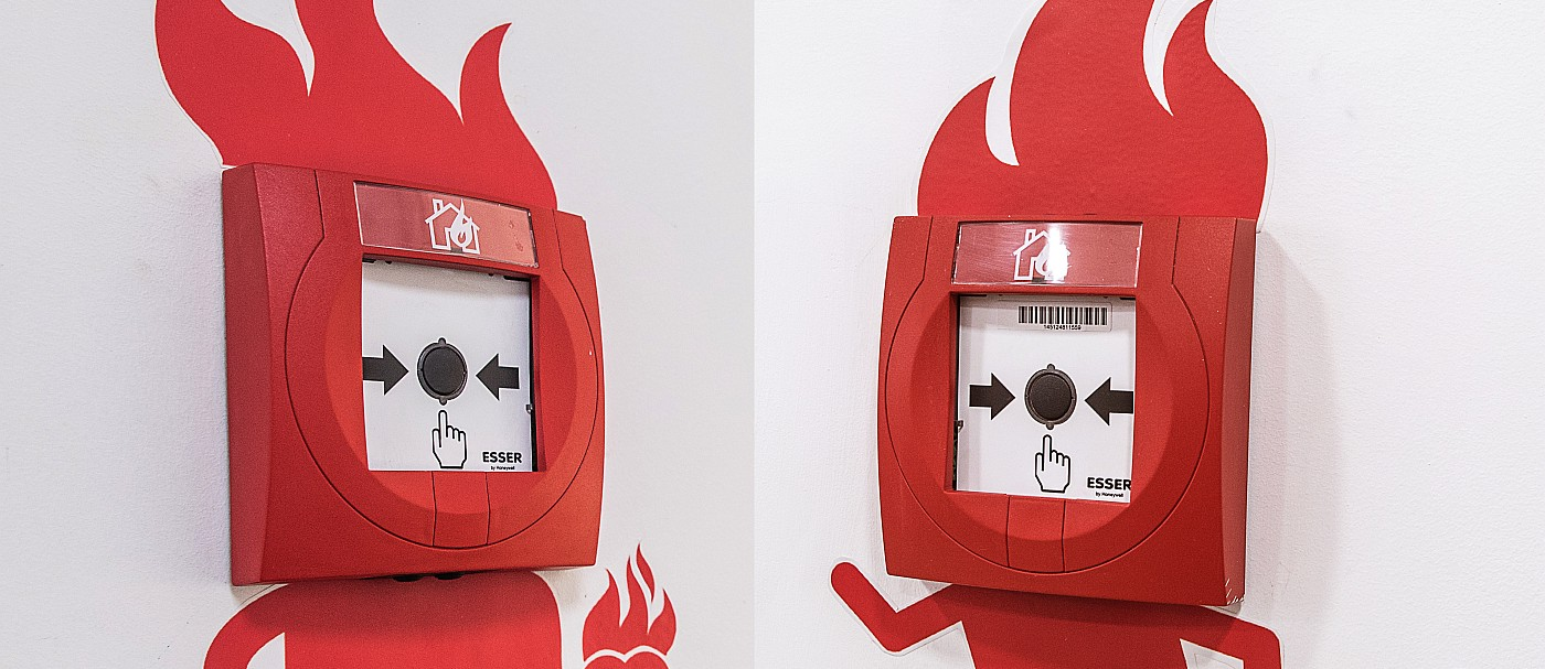 Fire alarm buttons surrounded by painting on the wall