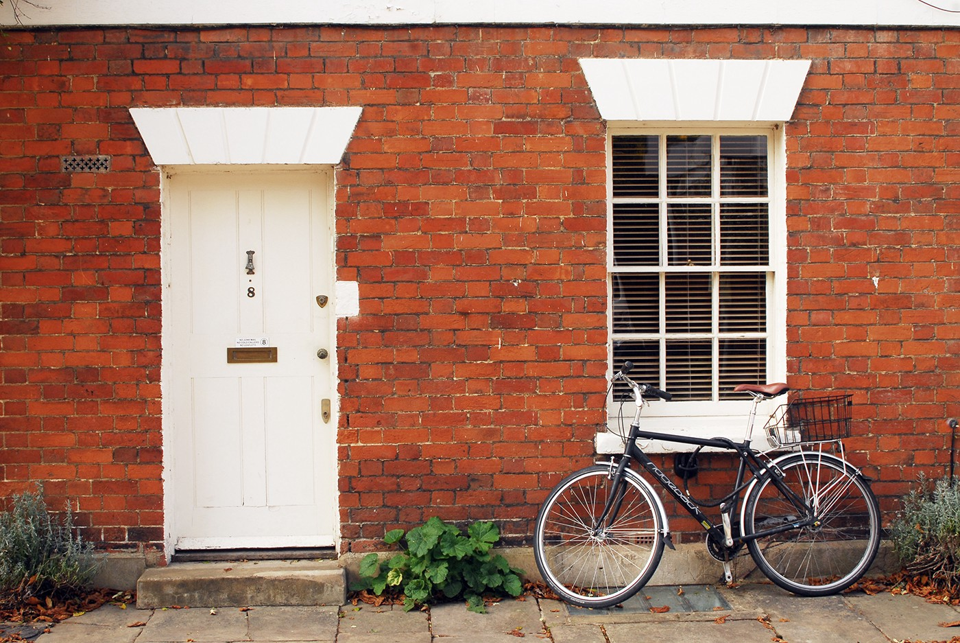 Red brick house with white door and bicycle leaning against the window