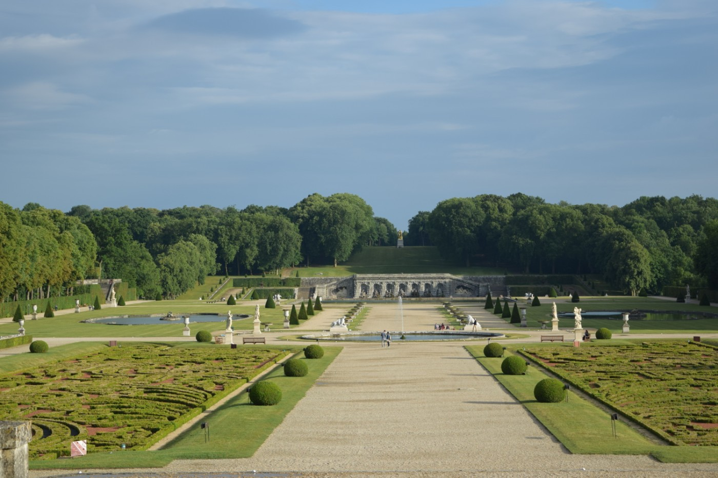 The grounds of the Château de Vaux-le-Vicomte (parterres, basins, grotto, statues) on a summer night.