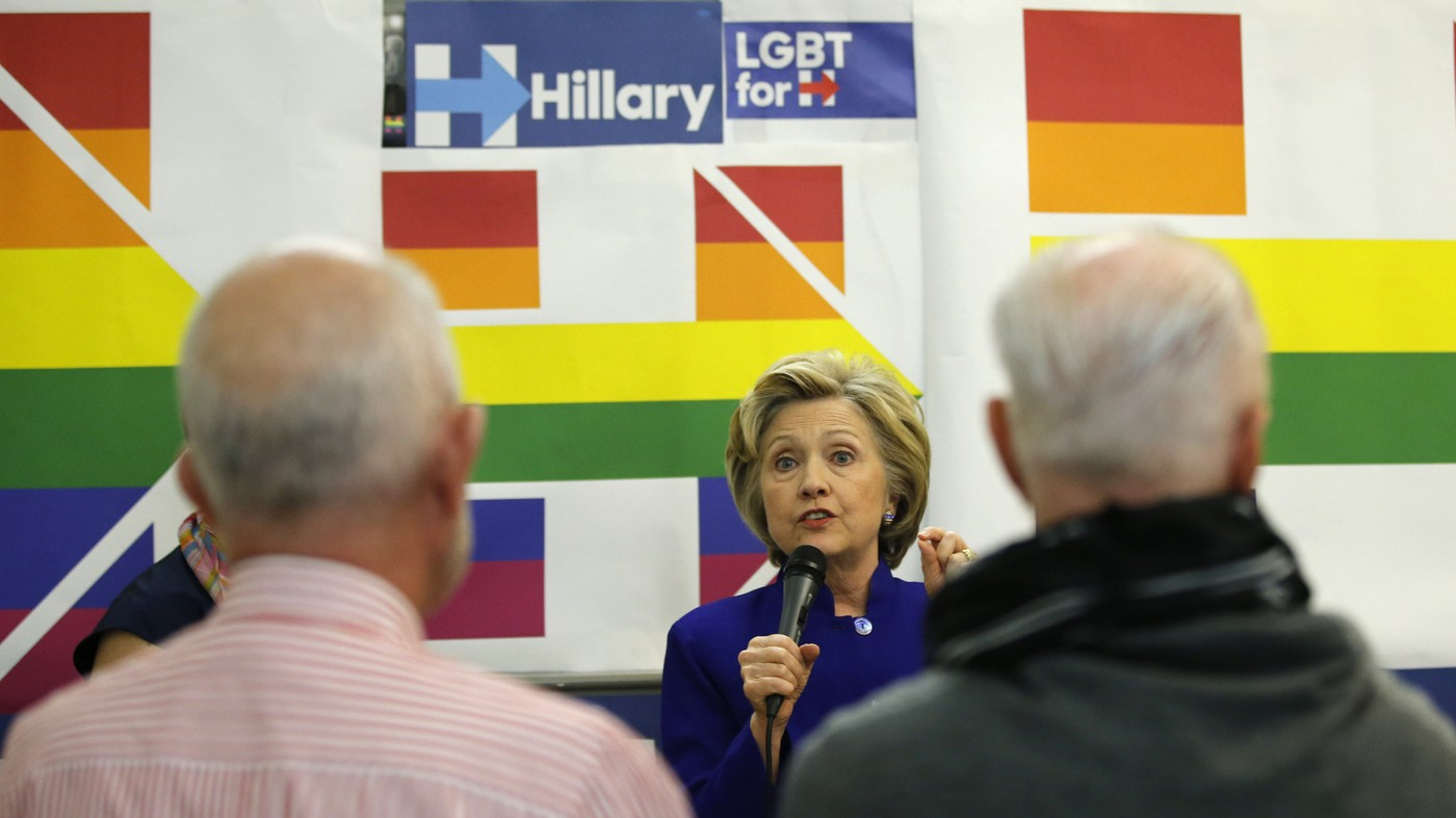 Kathy Willens/AP — Hillary Clinton using a mic, a rainbow version of her campaign logo behind her