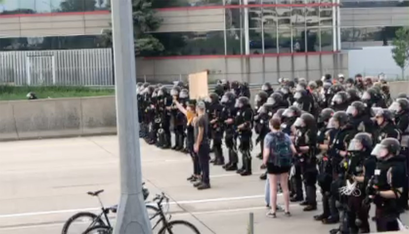 Three protestors stand in front of dozens of police during the Black Lives Matter protest.