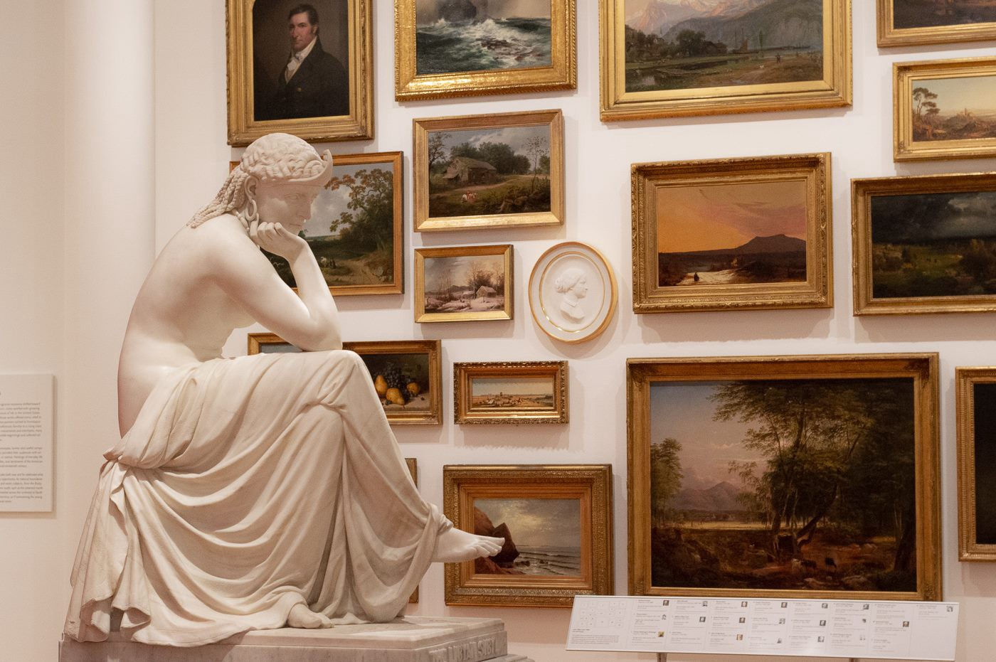 A neoclassical sculpture of a seated woman sits in front of a salon wall of paintings.