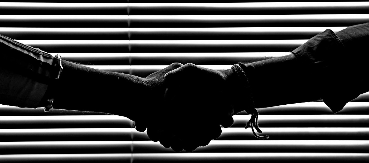 A handshake in front of a set of horizontal blinds