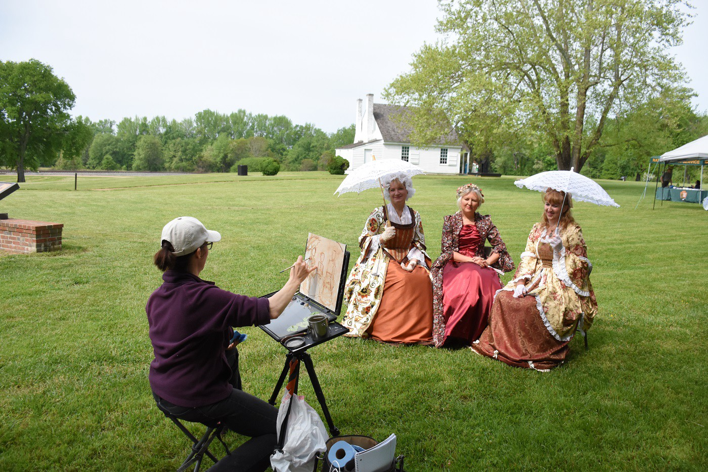 3 ladies dressed in Civil War era costumes sit while an artist paints their picture